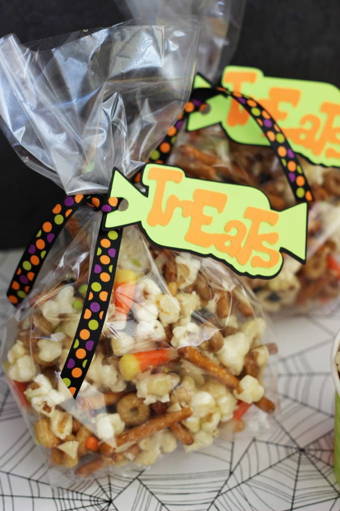 Gooey Halloween Popcorn Crunch - Popcorn, pretzels, candy corn, almonds, and cereal all mixed up in the most wonderfully addicting sugar coating!