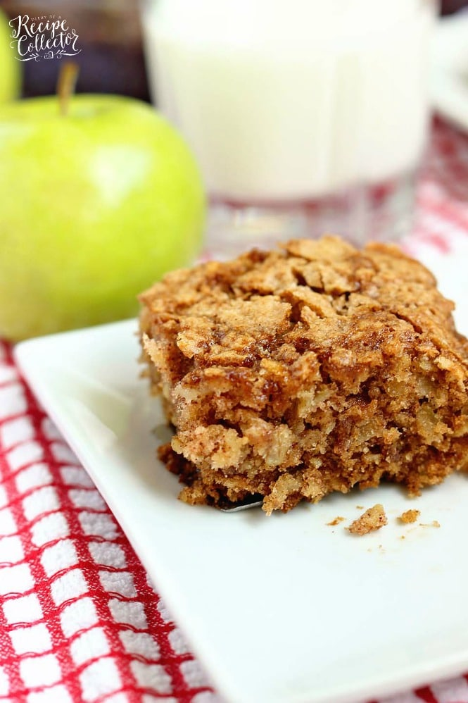 a square of golden brown cake with streusel topping on a white plate with a green apple in the background