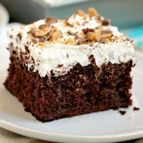 Best Ever Heath Bar Poke Cake - Chocolate cake soaked in sweetened condensed milk, caramel, and hot fudge and topped with heath bar bits and whipped cream. This is the easiest and most delicious make-ahead dessert ever!