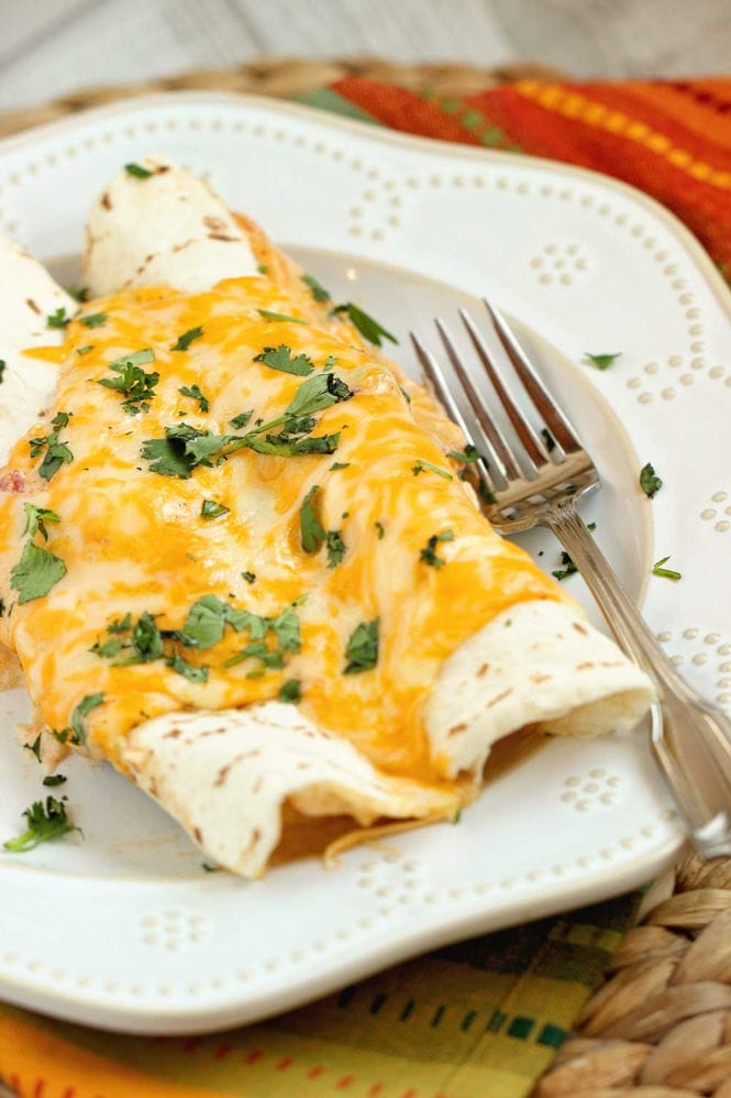 Cheesy Cajun Shrimp Enchiladas - Shrimp smothered in a homemade cheese sauce with Creole spices rolled into flour tortillas and baked.